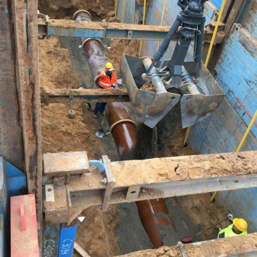 Die Steinzeugrohre für die Schmutzwasserkanäle wurden bis über Rohrscheitel mit steinfreiem Sand verfüllt. Danach konnte das Rohrauflager für die Betonrohre des Regenwassersammlers hergestellt werden. Foto: STRATIE Bau GmbH