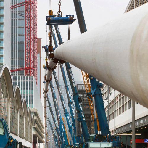 Eine 1500 m lange Stahl in Stahl Fernwärmeleitung AD 600 mm wird mitten im Zentrum von Rotterdam von 22 Kränen auf 14m Höhe gezogen. Foto: Visser & Smit Hanab bv