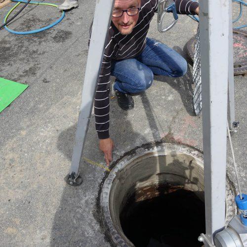 Peter Eschenbrenner zeigt auf die Markierung, die benötigt wird, um den Vertiliner® in der richtigen Position in den Schacht einzubauen. Foto: DIRINGER & SCHEIDEL ROHRSANIERUNG