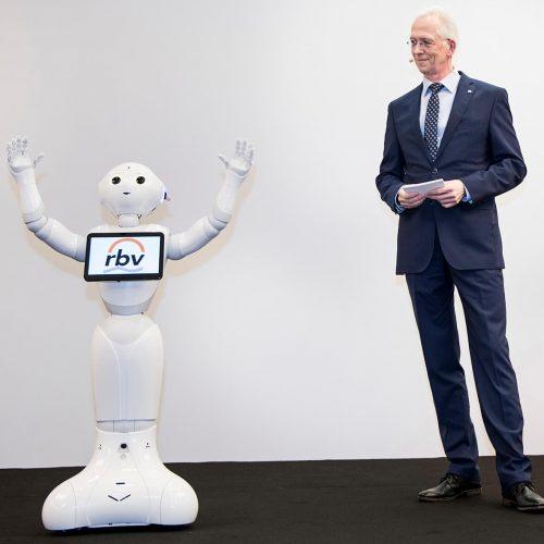"""rbv-Hauptgeschäftsführer Dieter Hesselmann versicherte sich bei der Moderation der Tagung der Unterstützung durch Pepper. Der humanoide Roboter ist darauf programmiert, nicht nur Sprache aufzunehmen und darauf zu antworten, sondern auch gleichzeitig den Gesichtsausdruck des Sprechenden zu """"interpretieren"""".  Foto: Rohrleitungsbauverband"""