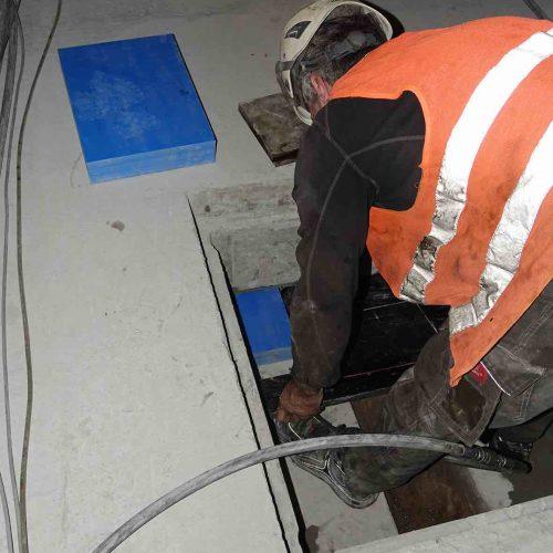 Unter Zuhilfenahme einer Schablone werden vier Sylodyn-Platten pro Schacht exakt an den vorgesehenen Stellen unterhalb des Troges platziert.  Foto: thyssenkrupp Infrastructure