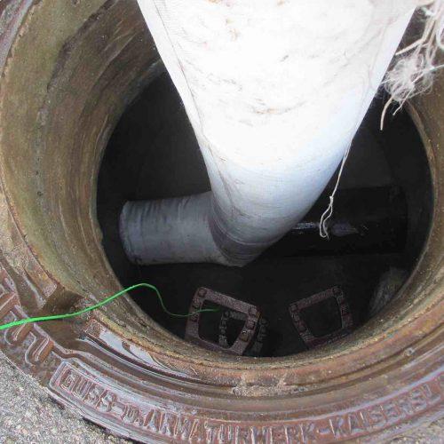 Einbringen des Schlauches über den Schacht in die Haltung. Das grüne Kabel dient zur Übertragung der Temperaturwerte an das Datenaufzeichnungsgerät. Foto: Güteschutz Kanalbau
