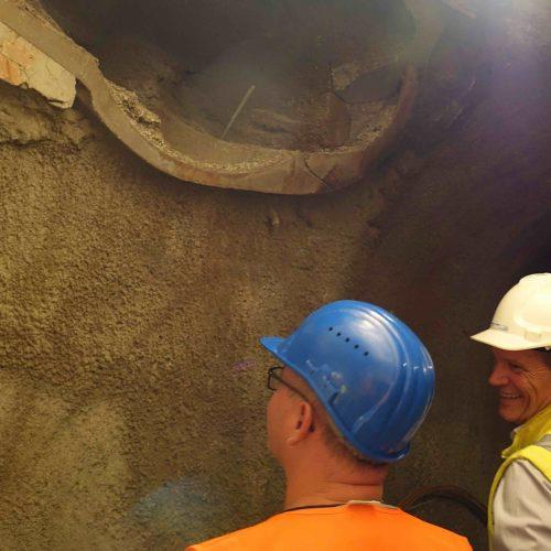 Die Überreste der alten Trinkwasserleitung sind noch deutlich zu erkennen. Techniker Heiko Nytsch, Stadtentwässerung Dresden GmbH (links) und Dipl.-Ing. Jens Uhlig, ACI-Aquaproject Consult erinnern sich an diese Überraschung im Untergrund und sind sich einig: Hier wäre jedes andere grabenlose Verfahren als der bergmännische Stollenvortrieb gescheitert. Foto: Güteschutz Kanalbau