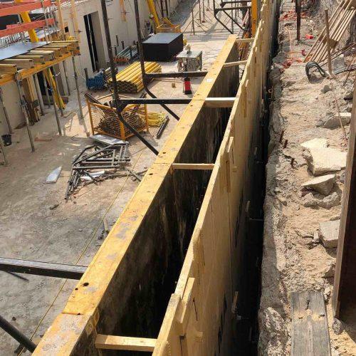 Im Rahmen einer effizienten Realisierung der Außenwände des Untergeschosses wurde eine Stahlblechsonderschalung als Vorstellschalung eingesetzt. Somit konnte die normalerweise bei beengten Platzverhältnissen erforderliche zeit- und materialaufwändige Auffütterung zwischen dem Verbau und der Außenkante der Außenwand entfallen. Foto: ULMA Construction GmbH / Nils Koenning