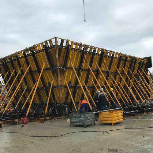 Die 60 Zentimeter starken schrägen Leichtbetonwände des Erdgeschosses, die innen glatt, nach außen aber abgestuft sind und hier die für das Gebäude charakteristische Holzstruktur aufweisen, wurde mit Sonderschalungselementen von ULMA erstellt. Foto: ULMA Construction