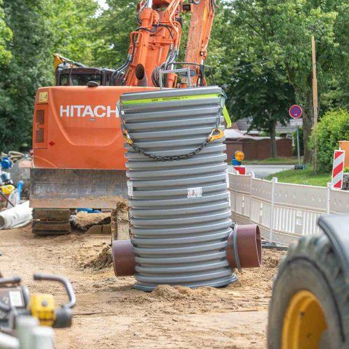 Die Sonderkonstruktion des Funke Schachtes DN 1000 mit dem kreisrunden (l.) und dem Eiprofil-Rohrspitzende (r.) steht in der Jorker Straße zum Einbau bereit.  Foto: Funke Kunststoffe