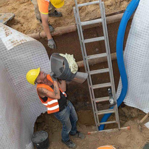 Der Funke BI-Adapter® Eiprofil wird zum Einbau in die Bestandsleitung in die Baugrube gereicht. Foto: Funke Kunststoffe