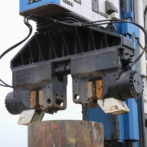 Zwei Klemmbacken haben das 800 Millimeter durchmessende Stahlrohr fest im Griff, um es in oder aus dem Boden zu vibrieren. Foto: thyssenkrupp Infrastructure